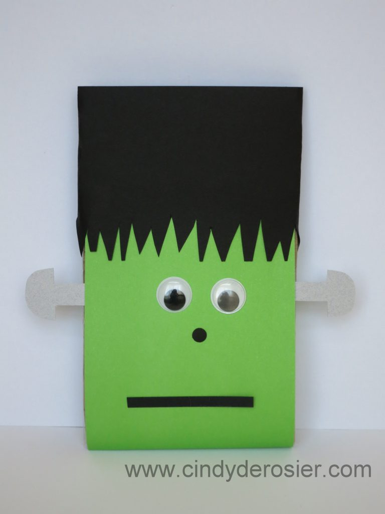 To make a Microwave Popcorn Frankenstein, you need: a package of microwave popcorn, cardstock or construction paper (green, black and silver/grey), large googly eyes, scissors, hole punch, and glue.