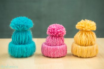 These tiny hats are made of yarn and toilet paper tubes.