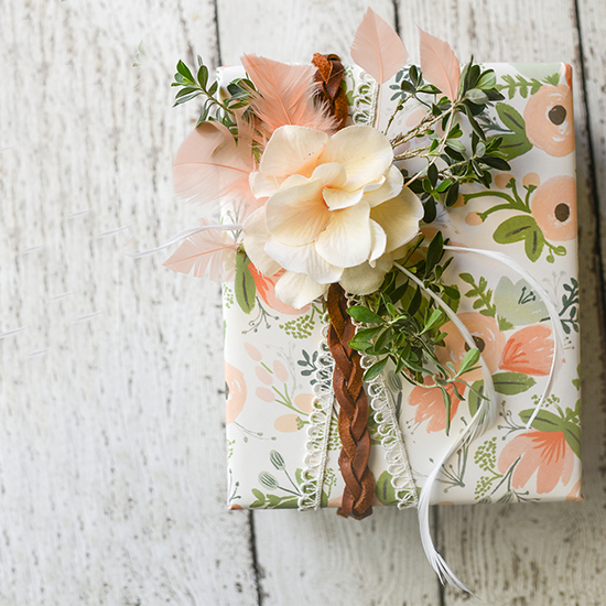 Boho inspired gift wrapping tutorial, using mixed materials, including leather, lace, feathers, flowers, and real greenery.