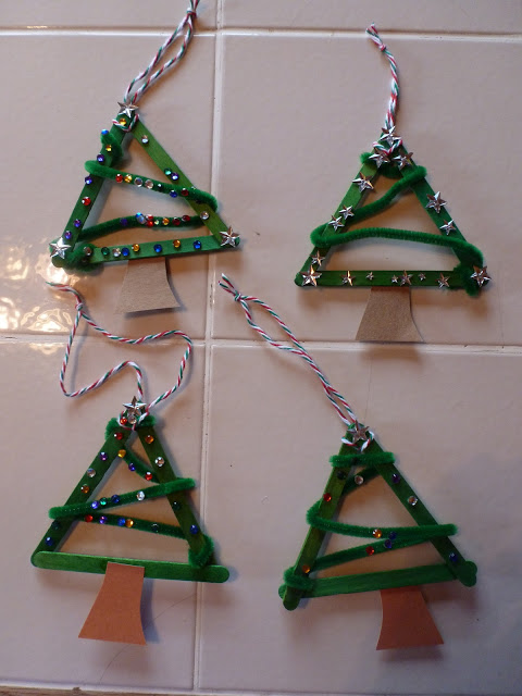 a simple tree ornament made from craft sticks, pipe cleaners and stickers