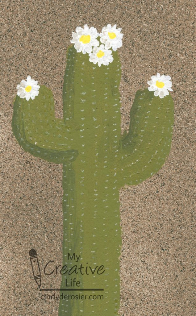 Paint a beautiful saguaro cactus on a textured sand surface.