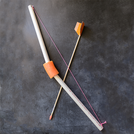 Use PVC pipe, a pool noodle, and string to make this toy bow. Tutorial for making the toy arrows, too.