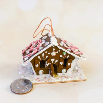Make a miniature gingerbread house ornament using polymer clay and puff paint.