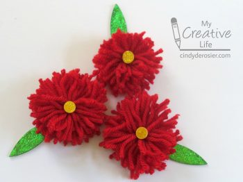 Top gifts with these cute yarn pom pom flowers.
