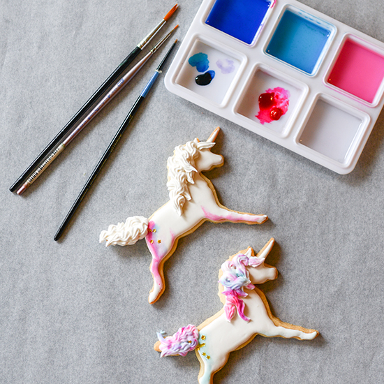 Unicorn sugar cookies iced in white royal icing, and then painted with watercolor style shading and details. Magical and delicious!